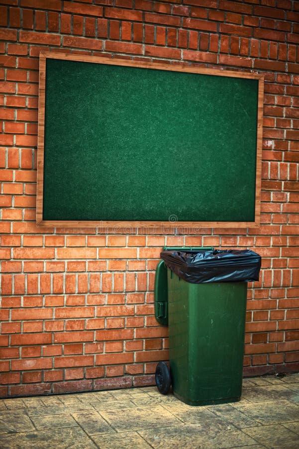 Τα πράσινα απορρίματα μπορούν με τη πλαστική τσάντα στοκ εικόνα