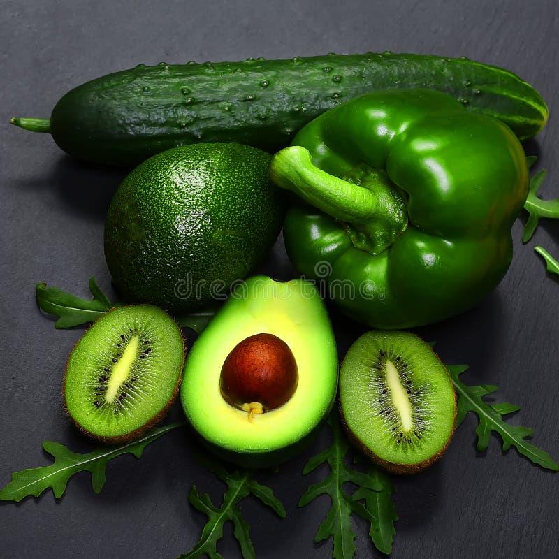 Τα πράσινα λαχανικά και τα φρούτα κατατάξεων, τα αβοκάντο, το ακτινίδιο, το πιπέρι και το αγγούρι σε έναν σχιστόλιθο επιβιβάζοντα στοκ εικόνα με δικαίωμα ελεύθερης χρήσης