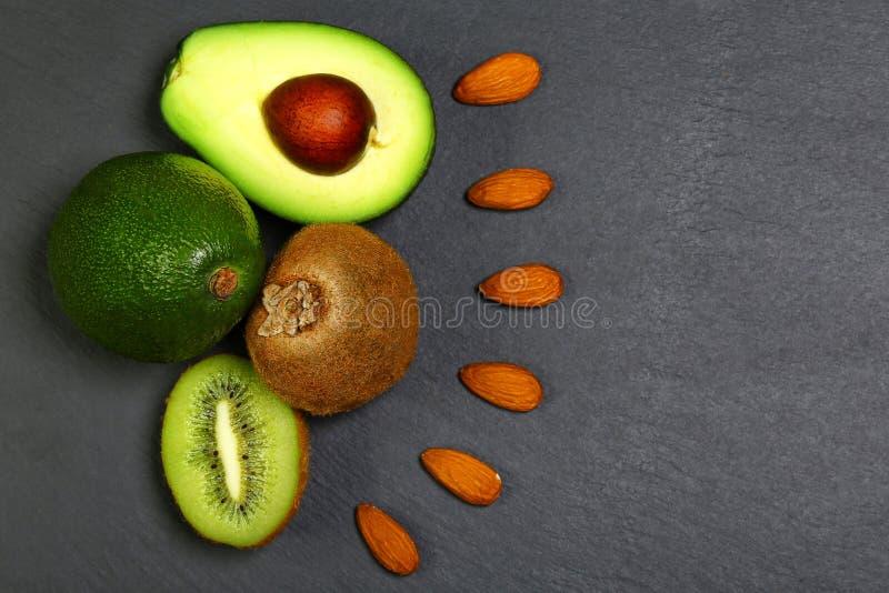 Τα πράσινα λαχανικά κατατάξεων και τα φρούτα, τα αβοκάντο, το ακτινίδιο και τα αμύγδαλα, καρύδια σε έναν σχιστόλιθο επιβιβάζονται στοκ εικόνες