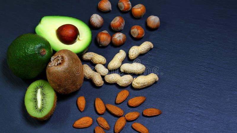 Τα πράσινα λαχανικά κατατάξεων και τα φρούτα, τα αβοκάντο, το ακτινίδιο και τα αμύγδαλα, φουντούκια, φυστίκια, καρύδια σε έναν πί στοκ εικόνες με δικαίωμα ελεύθερης χρήσης