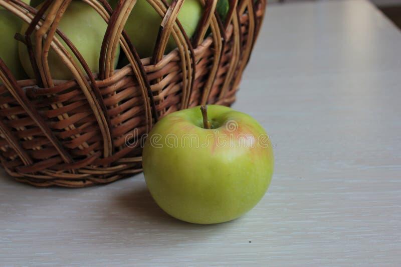Τα πράσινα μήλα βρίσκονται στο καλάθι και στον πίνακα στοκ φωτογραφία