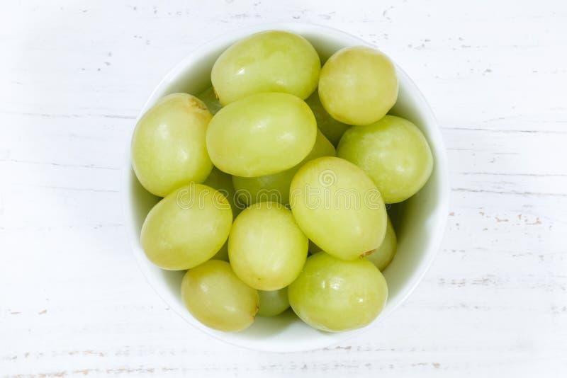 Τα πράσινα φρούτα φρούτων σταφυλιών κυλούν άνωθεν τον ξύλινο πίνακα στοκ φωτογραφία