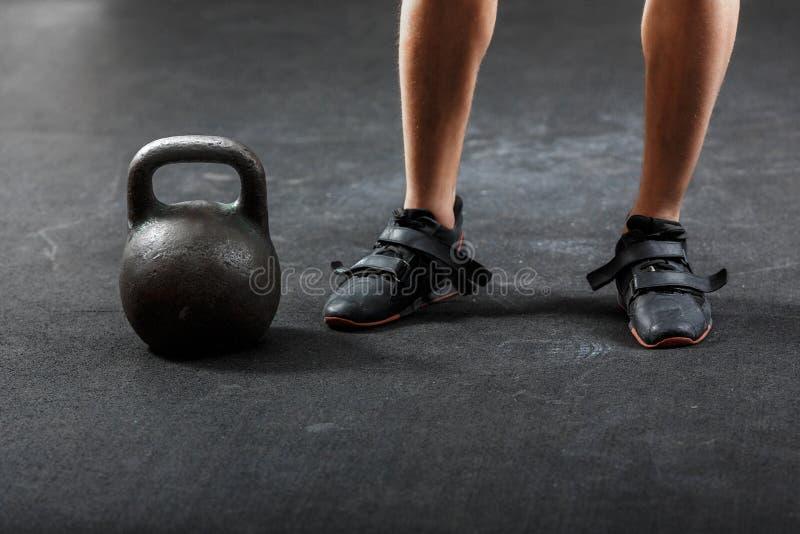 Τα πόδια ενός άντρα με μαύρα αθλητικά παπούτσια με μαύρο γυμναστικό κουδούνι στοκ φωτογραφία