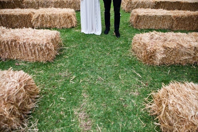 Τα πόδια νυφών και νεόνυμφων στέκονται στο γαμήλιο διάδρομο που γίνεται στοκ εικόνες
