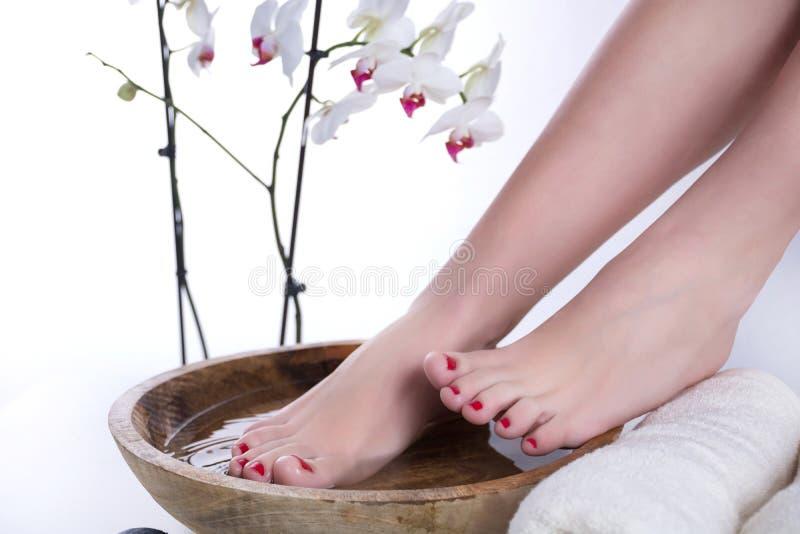 Τα πόδια στο ξύλινο κύπελλο με το νερό και την πετσέτα και την άσπρη ορχιδέα ανθίζουν στο υπόβαθρο στοκ φωτογραφία με δικαίωμα ελεύθερης χρήσης