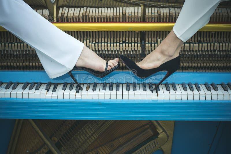 Τα πόδια στο πιάνο πληκτρολογούν το μπλε χρώμα, μόδα στοκ φωτογραφία