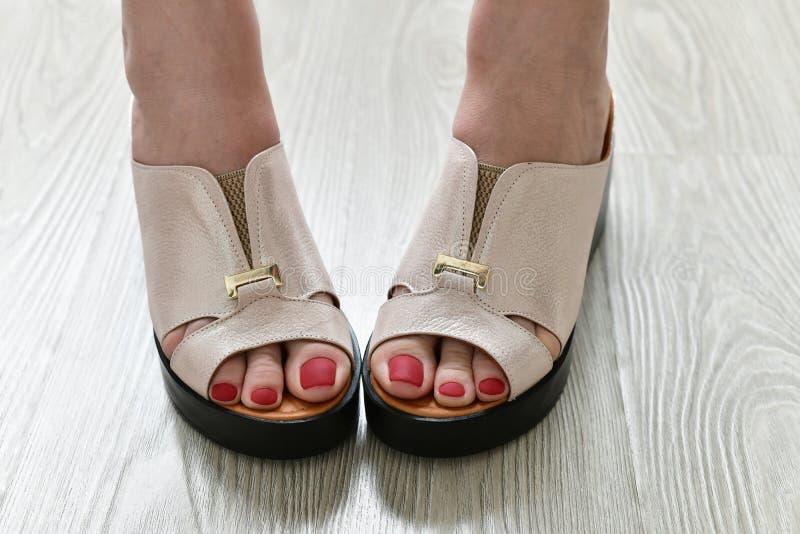 Τα πόδια των γυναικών θερινά άσπρα clogs στοκ εικόνες
