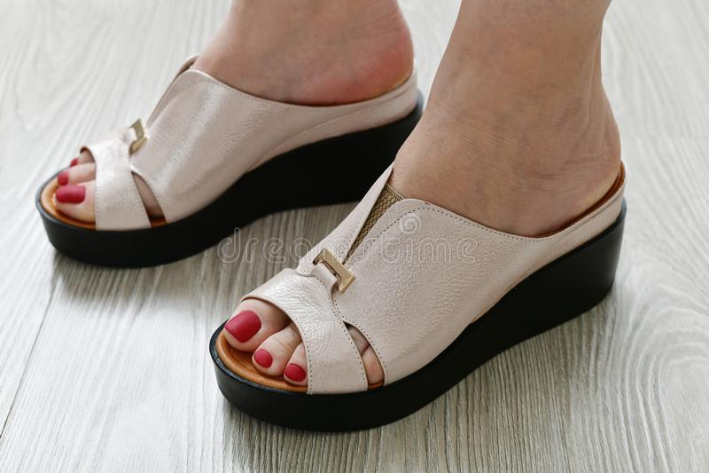 Τα πόδια των γυναικών θερινά άσπρα clogs στοκ εικόνα