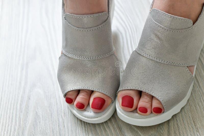 Τα πόδια των γυναικών στα θερινά άσπρα σανδάλια στοκ εικόνες