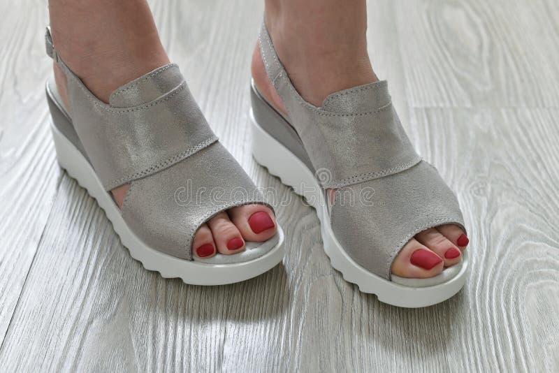 Τα πόδια των γυναικών στα θερινά άσπρα σανδάλια στοκ εικόνα