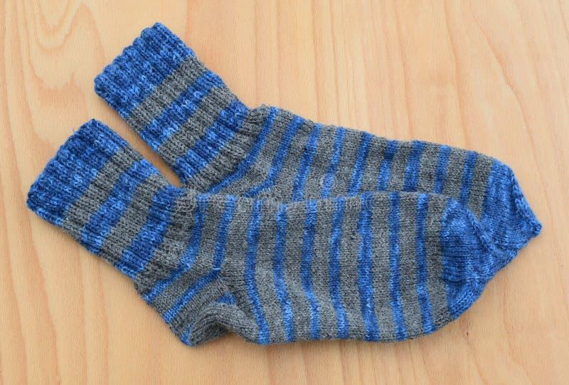 Τα πόδια υποβάθρου γκρίζα και το μπλε πλέκουν ένα ζευγάρι μαλλιού καλτσών προβάτων του θερμού άσπρου χειμερινού πυκνά στοκ φωτογραφία με δικαίωμα ελεύθερης χρήσης
