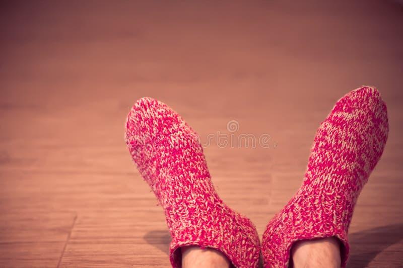Τα πόδια ατόμων στο κόκκινο μαλλί κτυπούν βίαια το αρσενικό έπλεξαν το χειμώνα ενδυμάτων στοκ φωτογραφίες