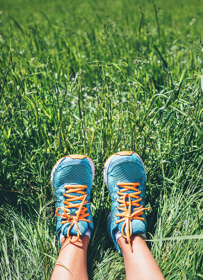 Τα πόδια γυναικών στα φωτεινά μπλε τρέχοντας παπούτσια είναι στην υψηλή πράσινη χλόη στοκ φωτογραφία με δικαίωμα ελεύθερης χρήσης