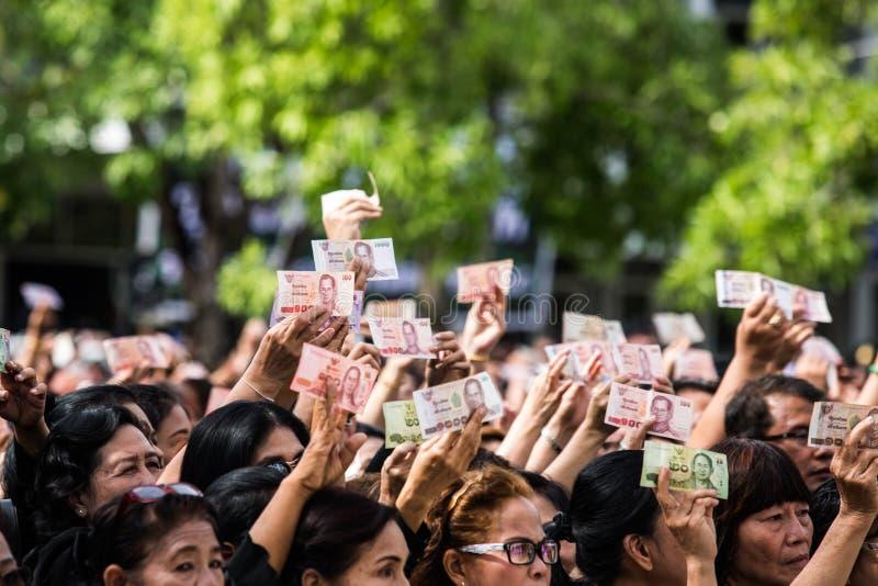 Τα πλήθη των θρηνητών κρατούν ότι τα ταϊλανδικά μετρητά για παρουσιάζουν εικόνα του βασιλιά Bhumibol κατά τη διάρκεια της τελετής στοκ φωτογραφίες