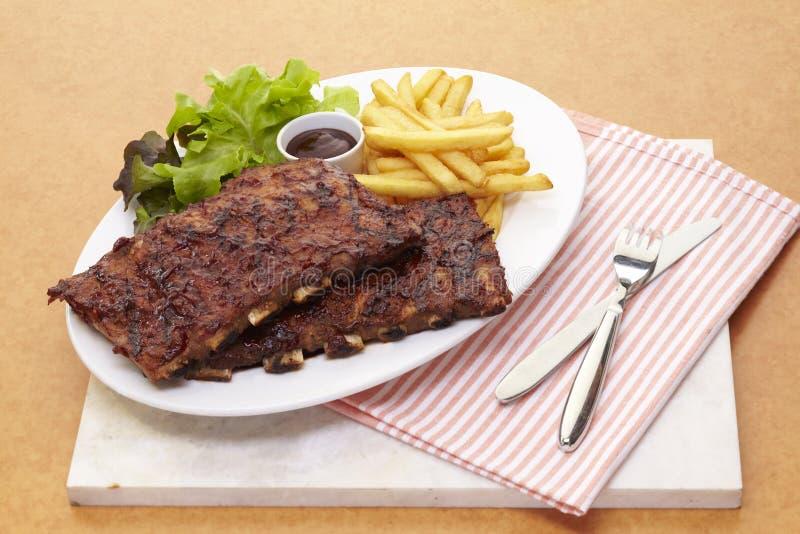 Τα πλευρά χοιρινού κρέατος σχαρών εξυπηρετούν με γαλλικό τηγανισμένο και τη σαλάτα στοκ εικόνες