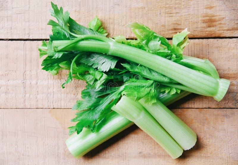 Τα ραβδιά σέλινου και βγάζουν φύλλα το φρέσκο λαχανικό - δέσμη του μίσχου σέλινου στο ξύλινο υπόβαθρο στοκ εικόνες με δικαίωμα ελεύθερης χρήσης