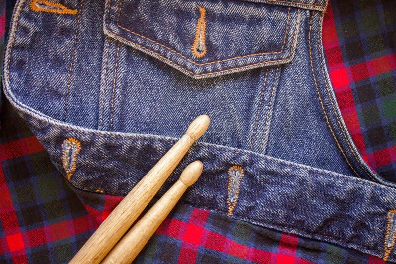 Τα ραβδιά τυμπάνων βρίσκονται σε ένα σκωτσέζικο κλουβί και τα τζιν στοκ φωτογραφία με δικαίωμα ελεύθερης χρήσης
