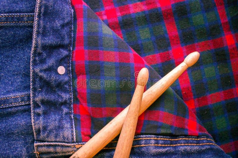 Τα ραβδιά τυμπάνων βρίσκονται σε ένα σκωτσέζικο κλουβί και τα τζιν στοκ εικόνα με δικαίωμα ελεύθερης χρήσης
