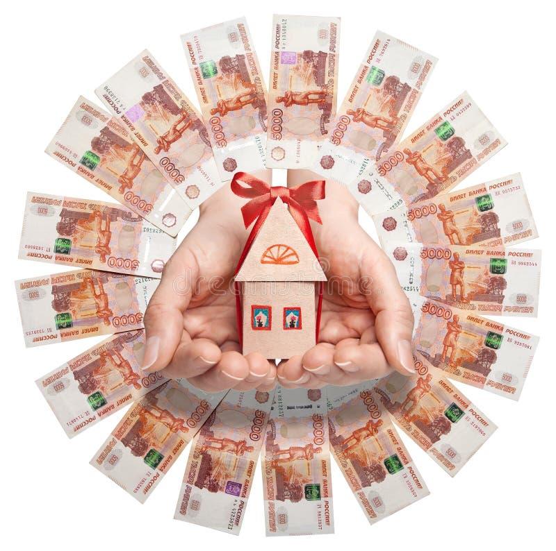 Τα ρωσικά τραπεζογραμμάτια τακτοποιούνται σε έναν κύκλο στο κέντρο του χεριού που κρατά ένα σπίτι εγγράφου με ένα κόκκινο τόξο στοκ εικόνες