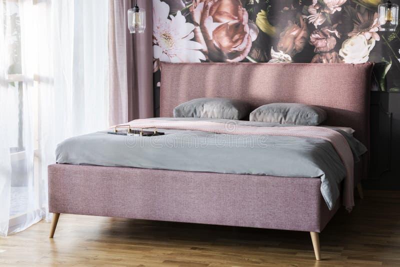 Τα ρόδινα γενικά και γκρίζα μαξιλάρια στο κρεβάτι στο φωτεινό εσωτερικό κρεβατοκάμαρων με το λουλούδι τυπώνουν στον τοίχο Πραγματ στοκ εικόνες