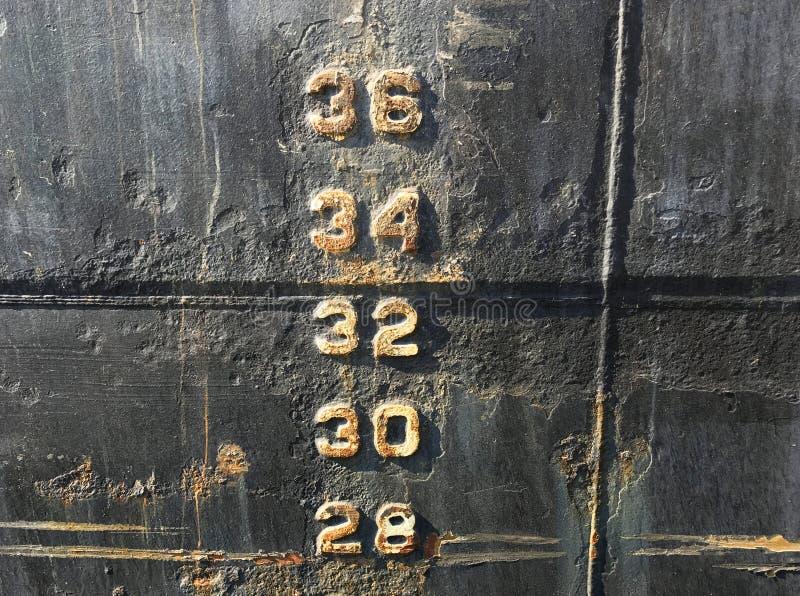 Τα σημάδια αριθμού μετρητών βάθους σταθμών ύδατος σε μια παλαιά μαύρη φλούδα σκαφών τεμαχίζουν στοκ εικόνες