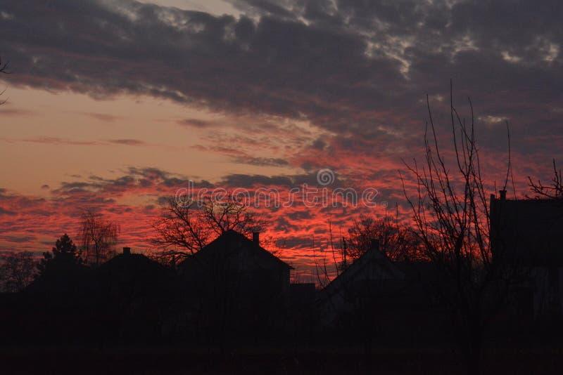 Τα σκοτεινά περιγράμματα των σπιτιών ενάντια στον ουρανό που καίει το ηλιοβασίλεμα στοκ φωτογραφία