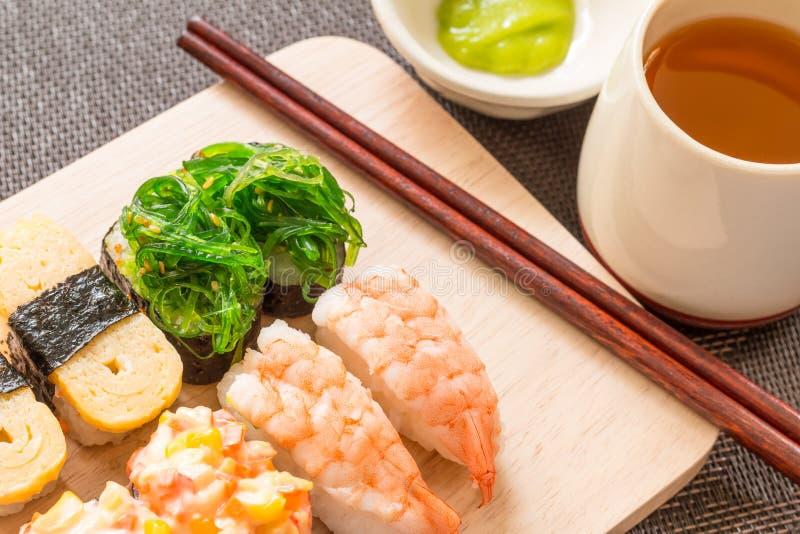 Τα σούσια που τέθηκαν με τα ραβδιά μπριζολών, wasabi εξυπηρέτησαν στην ξύλινη πλάκα, selec στοκ εικόνα με δικαίωμα ελεύθερης χρήσης