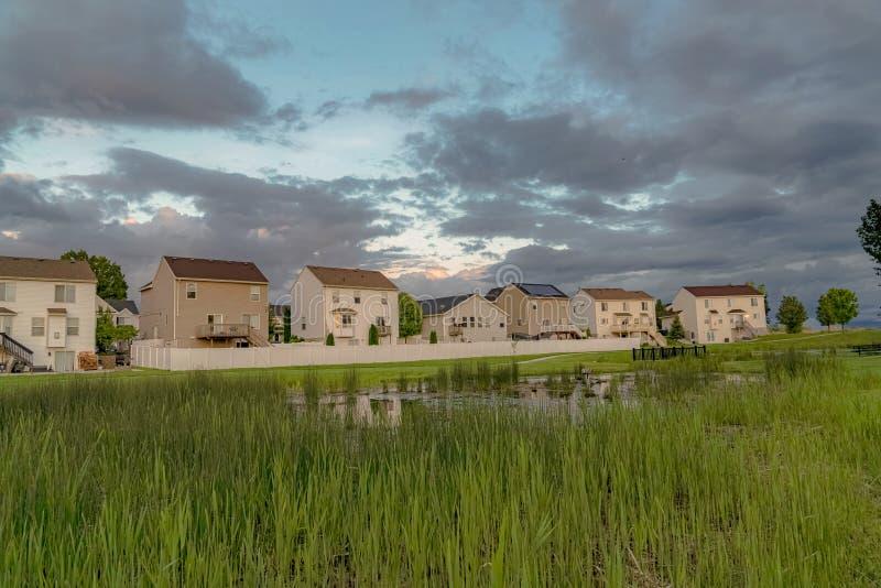 Τα σπίτια με τα μπαλκόνια και μια άποψη της χλοώδους λίμνης γεφυρώνουν και επεκτατικός πράσινος τομέας στοκ φωτογραφίες με δικαίωμα ελεύθερης χρήσης