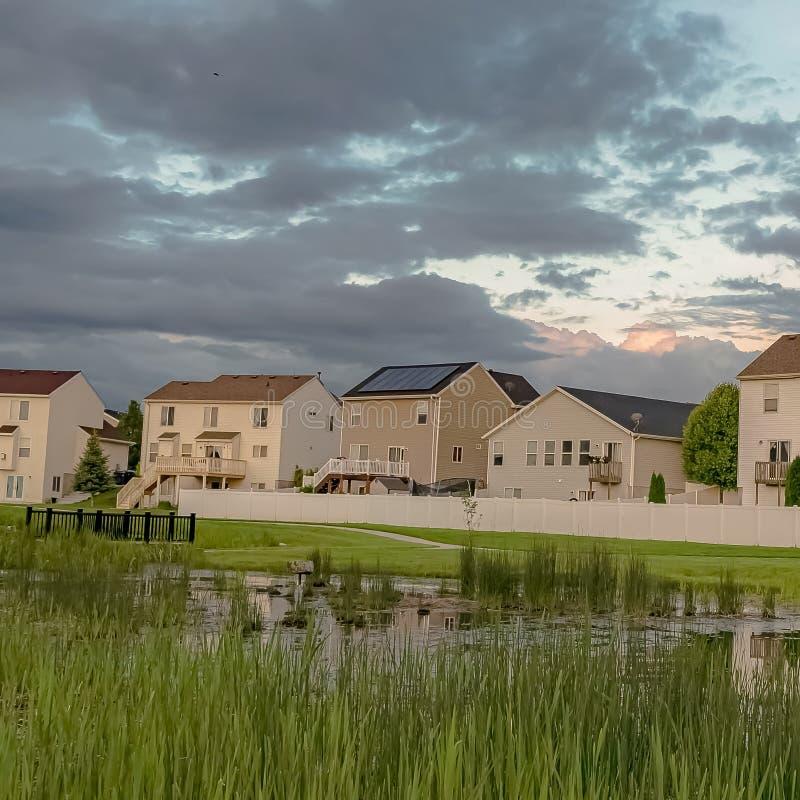 Τα σπίτια πλαισίων με τα μπαλκόνια και μια άποψη της χλοώδους λίμνης γεφυρώνουν και επεκτατικός πράσινος τομέας στοκ εικόνες