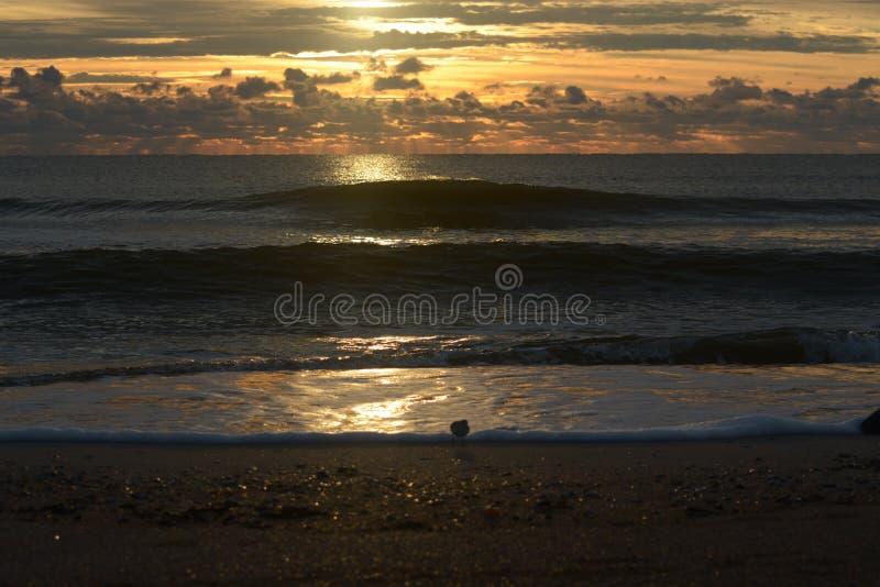 Τα σπασίματα ανατολής μέσω της κάλυψης σύννεφων και λάμπουν το φως του στα ωκεάνια κύματα κατωτέρω στοκ εικόνες