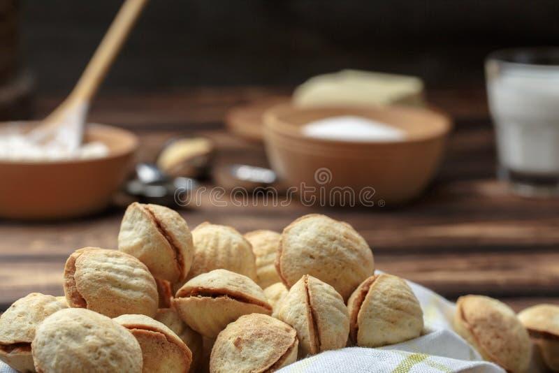 Τα σπιτικά διαμορφωμένα μπισκότα καρύδια με την κρέμα έβρασαν το συμπυκνωμένο γάλα στον ξύλινο πίνακα Αγροτικό ύφος Μακροεντολή κ στοκ φωτογραφίες