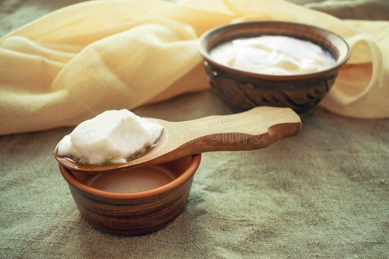 Τα σπιτικά kefir γάλακτος σιτάρια σε ένα ξύλινο κουτάλι επάνω από έναν άργιλο κυλούν το ο στοκ φωτογραφία με δικαίωμα ελεύθερης χρήσης
