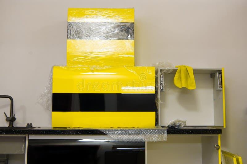 Τα στιλπνά κίτρινος-μαύρα χρώματα επίπλων κουζινών που προετοιμάζονται για συγκεντρώνουν εγκατάσταση των επίπλων κουζινών από μόν στοκ εικόνες