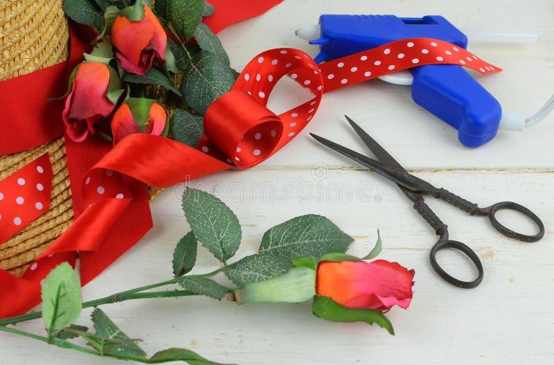 Τα στοιχεία για να διακοσμήσουν ένα καπό περιλαμβάνουν ένα καπέλο αχύρου, ένα εκλεκτής ποιότητας ψαλίδι, τα τριαντάφυλλα μεταξιού στοκ εικόνες