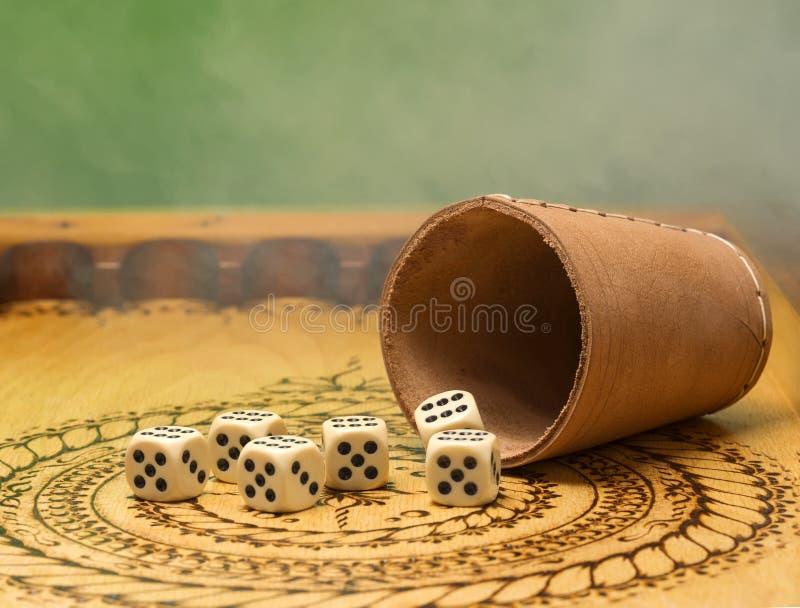 Τα στοιχεία του παιχνιδιού σε έναν χαρασμένο ξύλινο πίνακα λογαριάζουν πέντε, το πράσινους υπόβαθρο και τον καπνό στοκ φωτογραφία με δικαίωμα ελεύθερης χρήσης