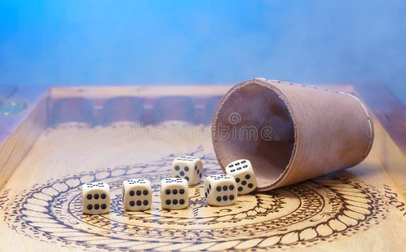 Τα στοιχεία του παιχνιδιού σε έναν χαρασμένο ξύλινο πίνακα λογαριάζουν έξι, το μπλε υπόβαθρο και τον καπνό στοκ φωτογραφίες