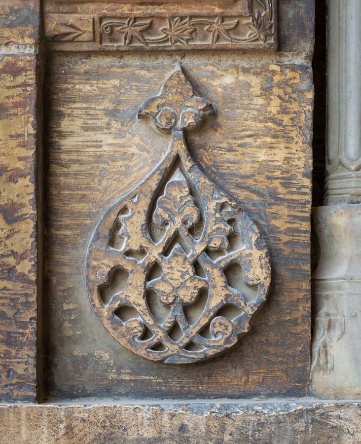 Τα στρογγυλά floral σχέδια που πλαισιώθηκαν από τα γεωμετρικά σχέδια χάρασαν στον εξωτερικό τοίχο του μουσουλμανικού τεμένους Has στοκ εικόνες