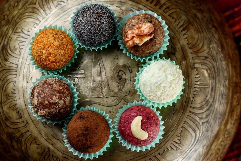 Τα στρογγυλά vegan γλυκά με τα καρύδια, καρύδα ξεφλουδίζουν, σπόροι παπαρουνών και ξηροί καρποί σε ένα όμορφο τραγουδώντας κύπελλ στοκ φωτογραφία