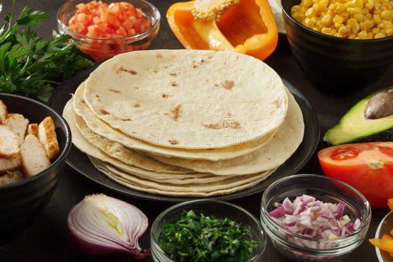 Τα συστατικά για το μεξικάνικο περικάλυμμα τσιμπάνε: pita, vegetales, κρέας κοτόπουλου στον πίνακα στοκ εικόνα