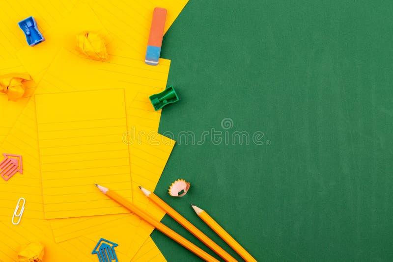 Τα σχολικά χαρτικά και το πορτοκαλί φύλλο του εγγράφου βρίσκονται στον πράσινο σχολικό πίνακα διαμορφώνοντας ένα πλαίσιο για το κ στοκ φωτογραφία με δικαίωμα ελεύθερης χρήσης