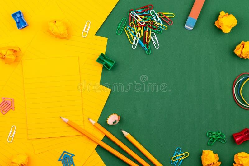 Τα σχολικά χαρτικά και το πορτοκαλί φύλλο του εγγράφου βρίσκονται στον πράσινο σχολικό πίνακα διαμορφώνοντας ένα πλαίσιο για το κ στοκ φωτογραφία