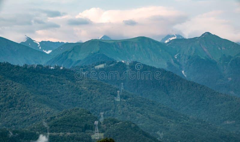 Τα σύννεφα και η ομίχλη στις κλίσεις του βουνού κυμαίνονται με τις χιονώδεις αιχμές το καλοκαίρι στοκ φωτογραφία