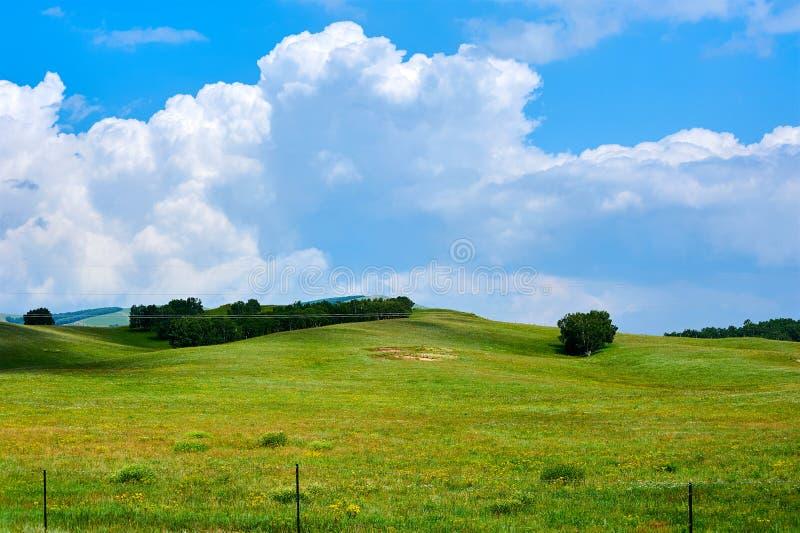 Τα σύννεφα και οι λόφοι και δέντρα στοκ εικόνες