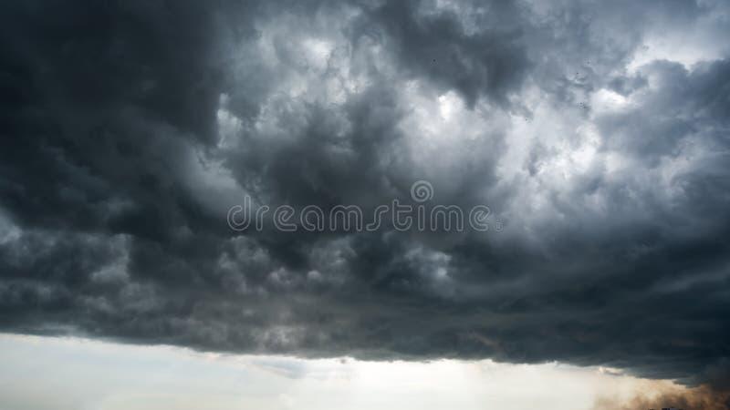 Τα σύννεφα με το υπόβαθρο, φως του ήλιου μέσω του πολύ σκοτεινού υποβάθρου σύννεφων της σκοτεινής θύελλας καλύπτουν, μαύρο υπόβαθ στοκ εικόνες