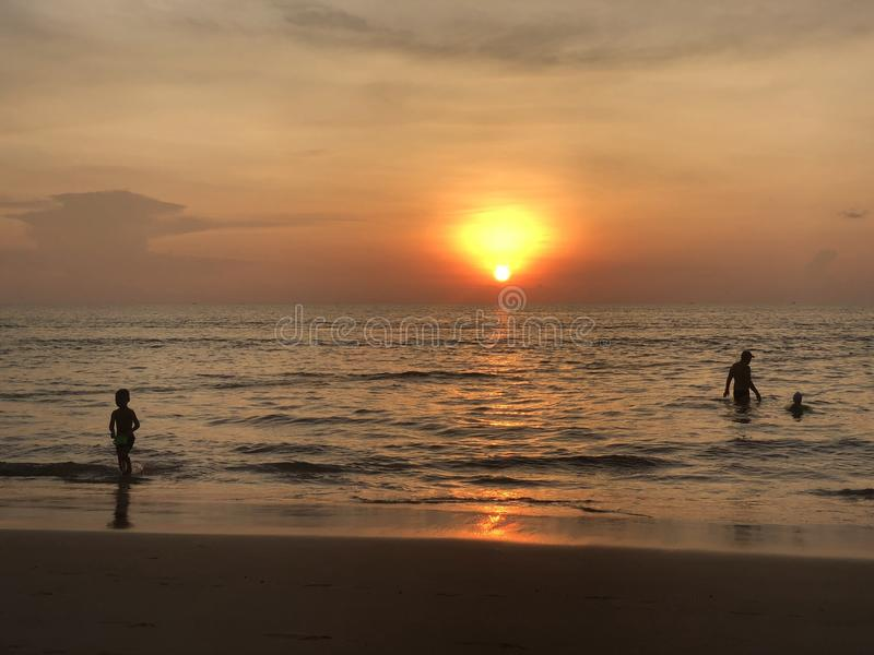 Τα σύνολα ήλιων στον ορίζοντα όπου η θάλασσα ενώνει τον ουρανό ο άνθρωπος-ενήλικος και παιδί-κολυμπά στη θάλασσα και απολαμβάνει  στοκ εικόνα