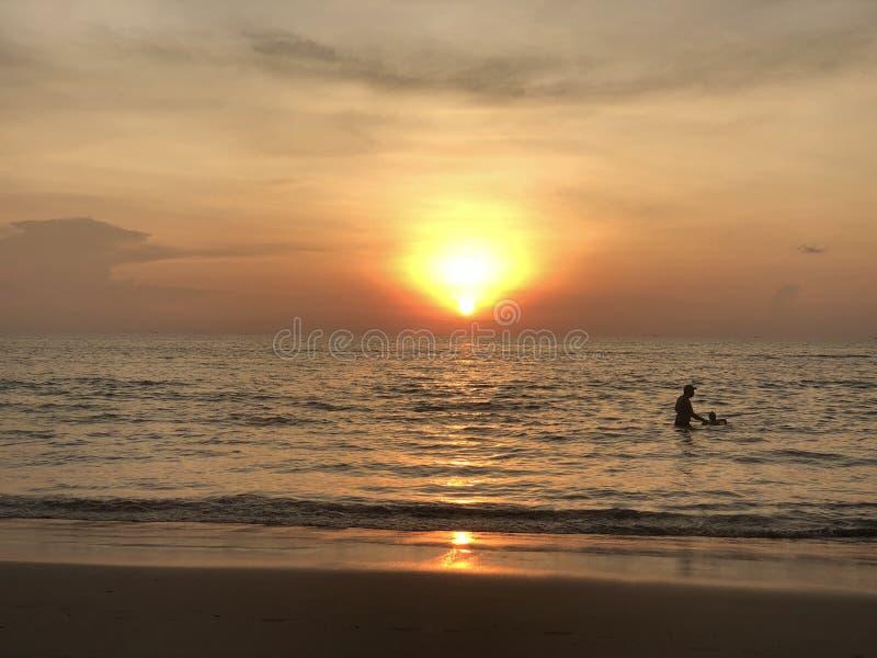 Τα σύνολα ήλιων στον ορίζοντα όπου η θάλασσα ενώνει τον ουρανό ο άνθρωπος-ενήλικος και παιδί-κολυμπά στη θάλασσα και απολαμβάνει  στοκ εικόνες με δικαίωμα ελεύθερης χρήσης