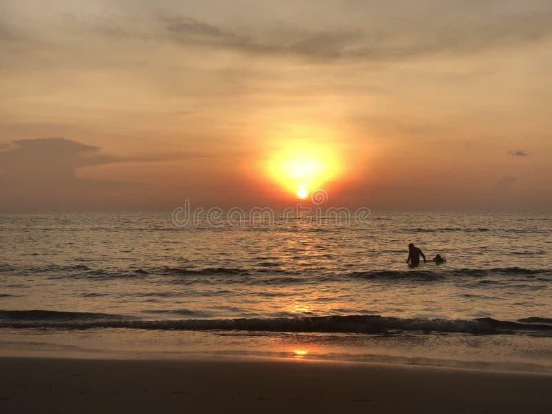 Τα σύνολα ήλιων στον ορίζοντα όπου η θάλασσα ενώνει τον ουρανό ο άνθρωπος-ενήλικος και παιδί-κολυμπά στη θάλασσα και απολαμβάνει  στοκ φωτογραφίες με δικαίωμα ελεύθερης χρήσης