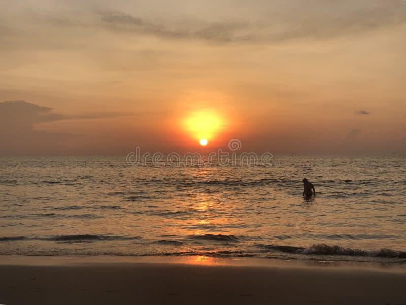 Τα σύνολα ήλιων στον ορίζοντα όπου η θάλασσα ενώνει τον ουρανό ο άνθρωπος-ενήλικος και παιδί-κολυμπά στη θάλασσα και απολαμβάνει  στοκ φωτογραφία με δικαίωμα ελεύθερης χρήσης