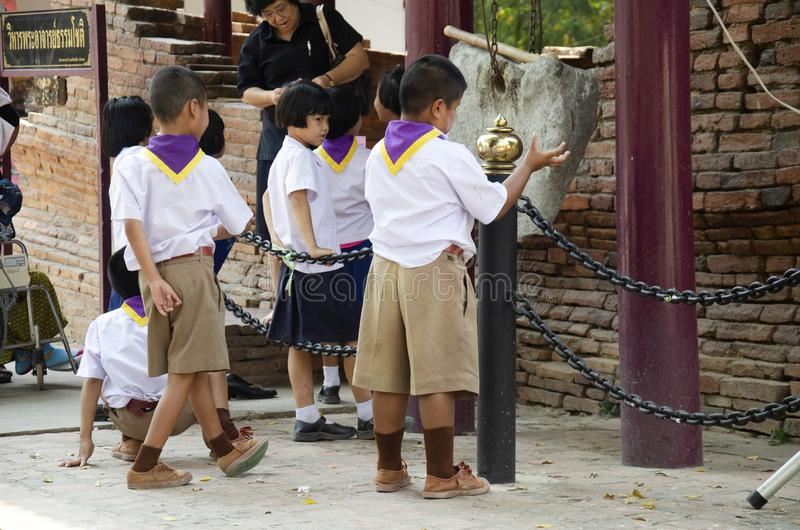 Τα ταϊλανδικά αγόρια και τα κορίτσια σπουδαστών η επίσκεψη και ο σεβασμός περπατήματος προσευμένος το άγαλμα του Βούδα στον τόνο  στοκ εικόνα