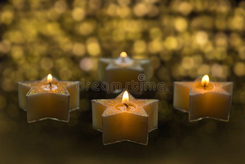 Τα τεσσάρων αστέρων διαμορφωμένα κεριά καίνε στο σκοτάδι στοκ εικόνα
